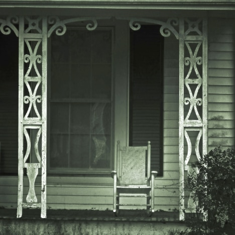 Old-fashioned photo of a rocking chair on an ornate porch